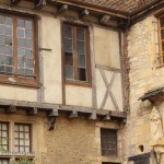 Exposed timber frame and stone building.